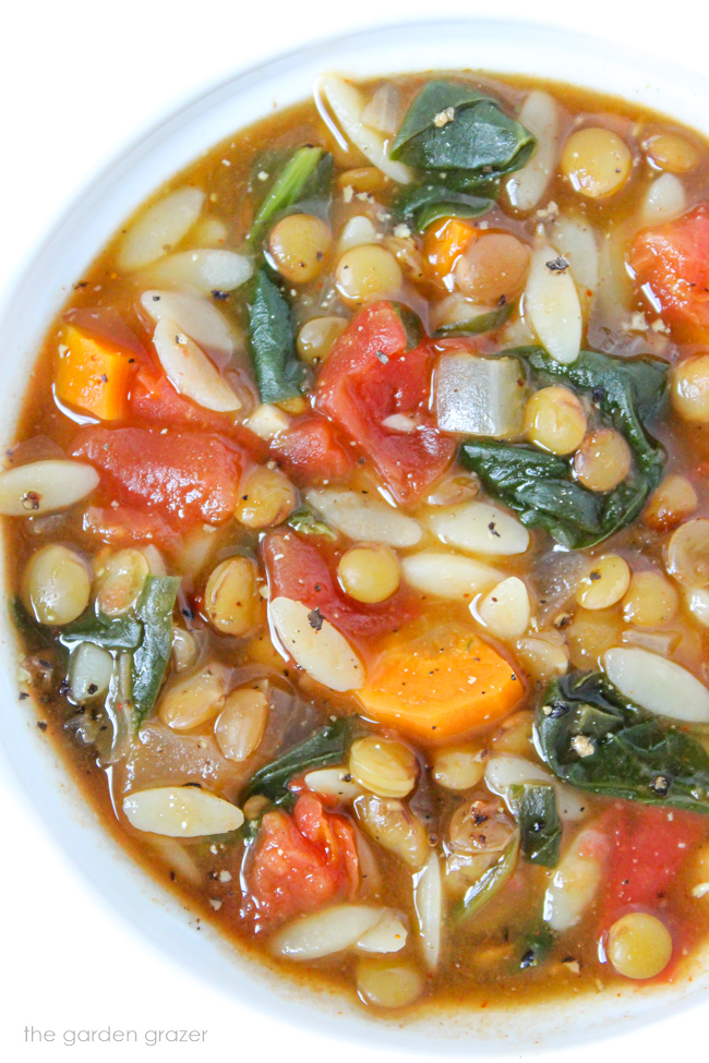 Bowl of vegan lentil orzo soup with spinach