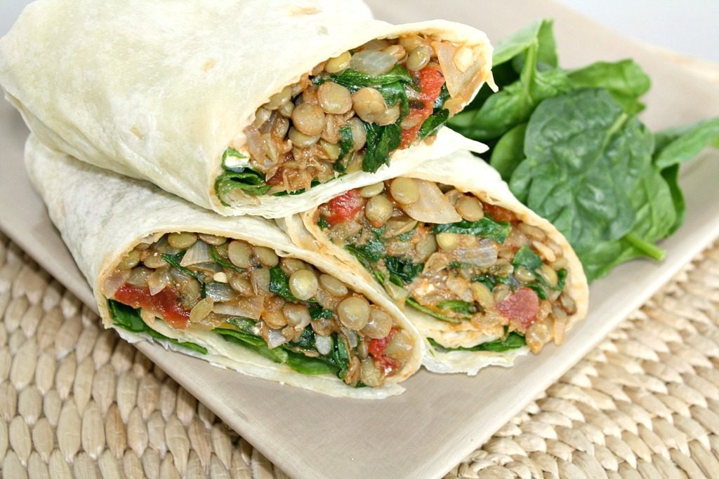 Lentil Spinach Burritos cut in half on a plate
