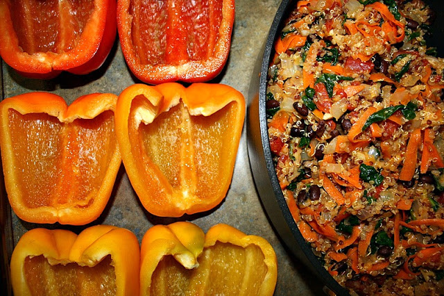 Bell pepper halves next to a pan of quinoa black bean filling