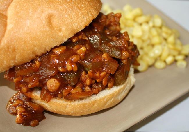 Vegan tempeh sloppy joes on a hamburger bun with a side of corn