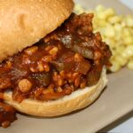 Vegan tempeh sloppy joes on a bun with a side of corn
