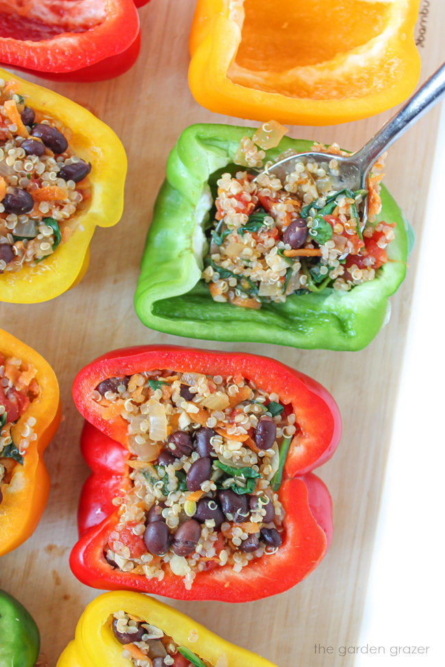 Spoon filling bell pepper halves with quinoa and black bean mixture