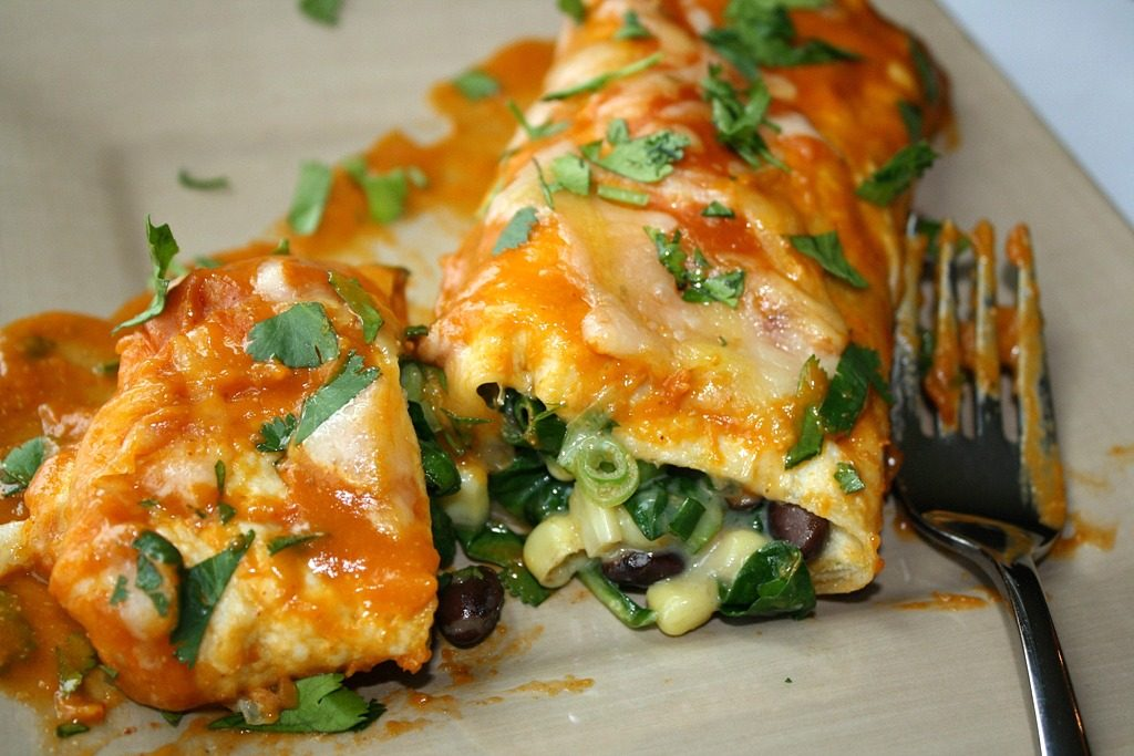 Vegan black bean spinach enchiladas on a plate with fork