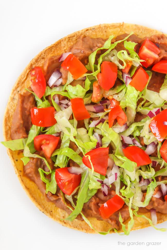 Vegan bean tostada with lettuce, tomato, and onion