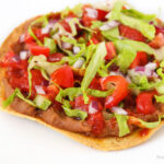 Vegan bean tostada topped with lettuce and tomato