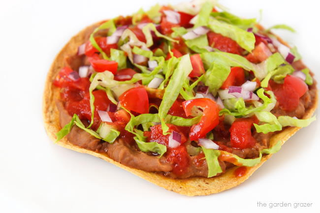 Bean tostada with salsa, lettuce, and tomato