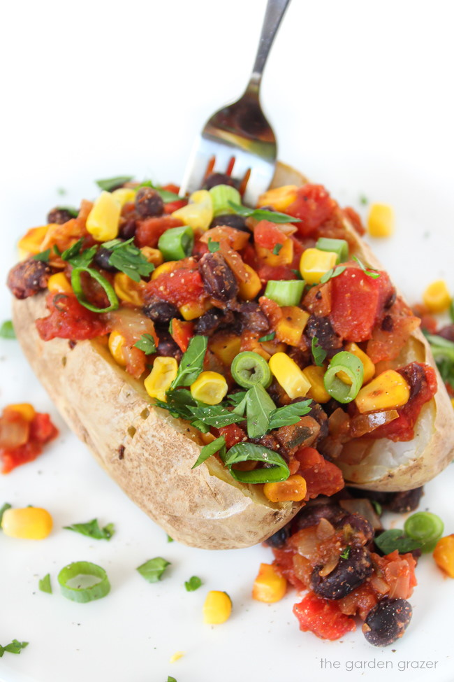 Baked potato topped with black beans, corn, and tomato on a white plate with fork