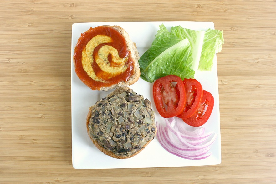 Black bean mushroom burger on a plate with assorted toppings