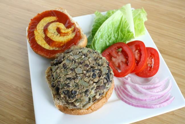 Vegan black bean mushroom burger on a bun with toppings