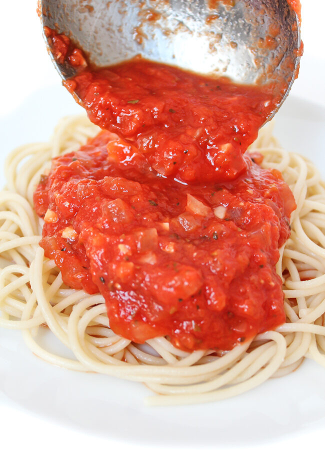 Marinara sauce being poured over spaghetti on a plate