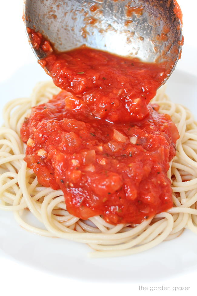 Marinara sauce being poured over spaghetti pasta on a plate