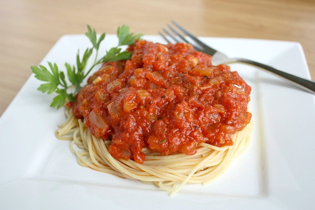 Plate of spaghetti noodles with homemade marinara sauce on top