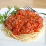 Spaghetti on a white plate topped with oil-free marinara sauce