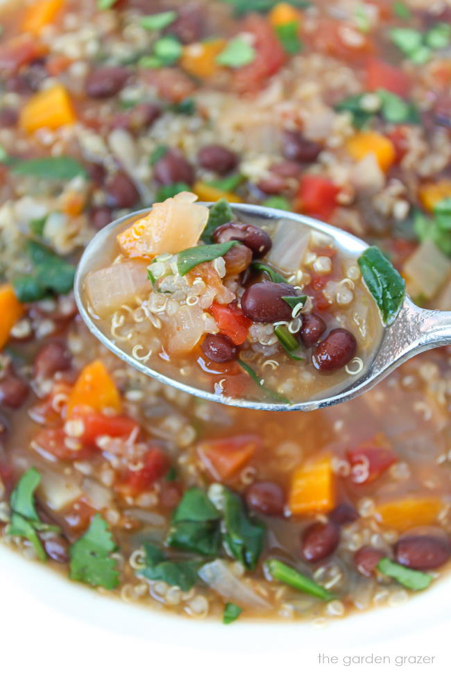 Spoonful of vegan quinoa black bean soup with spinach