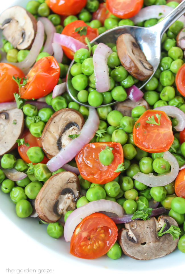 Vegan roasted peas and tomato in a bowl with spoon