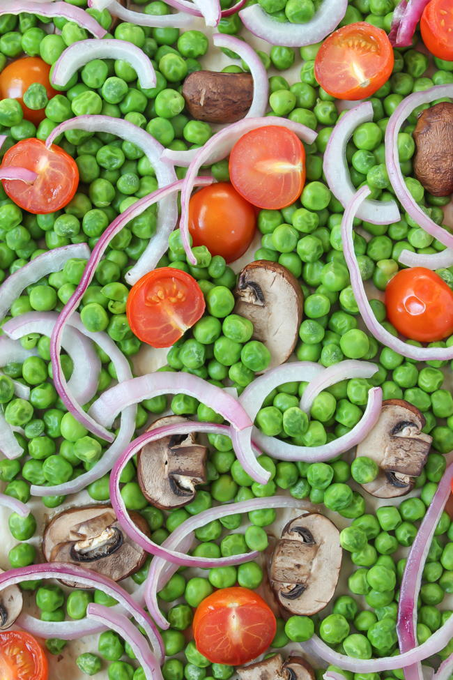 Sheet pan with roasted peas, mushrooms, tomato, and onion