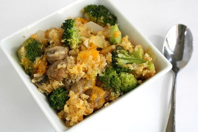 Vegan cheesy quinoa casserole in a small white bowl with spoon
