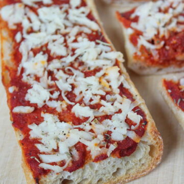 Vegan French bread cheese pizza on a cutting board