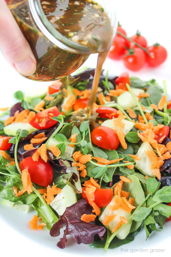 Pouring garlic balsamic dressing over a tossed salad