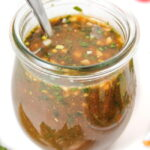 Oil-free garlic basil balsamic dressing in a small jar with spoon