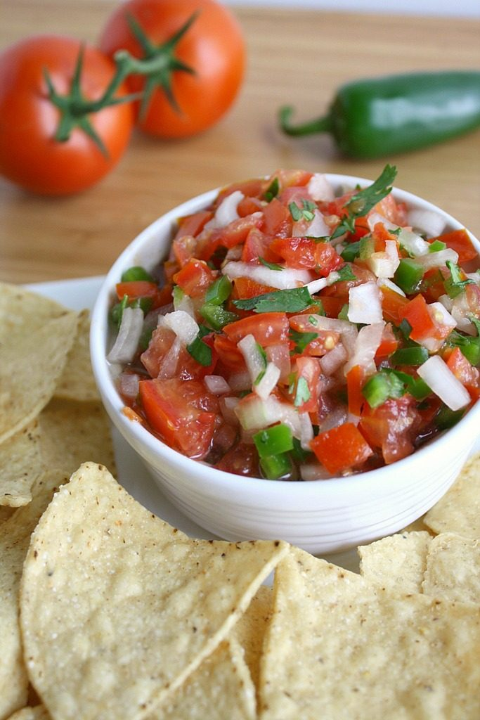 Fresh pico de gallo in a bowl with chips for dipping