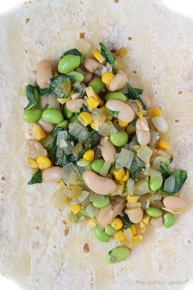 Open tortilla with enchilada filling of white beans, edamame, and corn