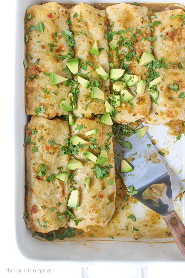 Pan of vegan green enchiladas topped with avocado and cilantro
