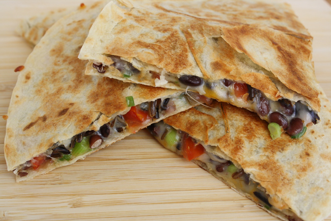 black bean quesadilla with tomato on a cutting board