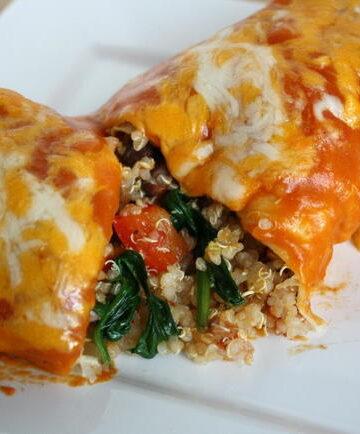 Vegan vegetable quinoa enchilada cut open on a white plate
