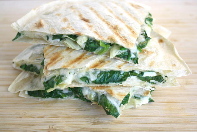 Cooked spinach artichoke quesadillas stacked on top of one another