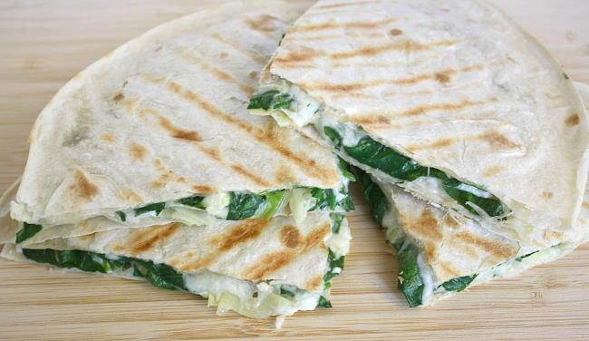 Vegan spinach quesadillas cut in half on a cutting board