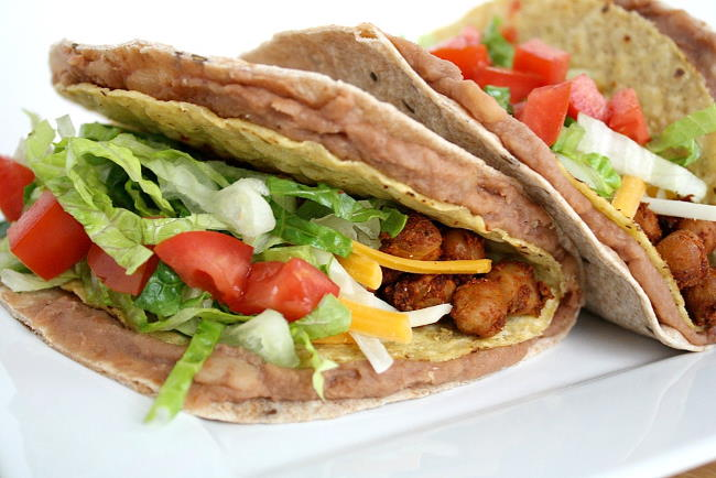 Vegan double decker chickpea tacos on a plate with lettuce and tomato