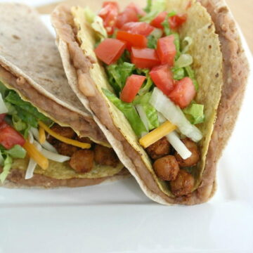 Two double decker chickpea tacos on a white plate