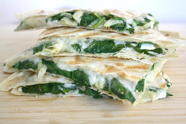Stacked vegan spinach artichoke quesadillas on a wooden cutting board