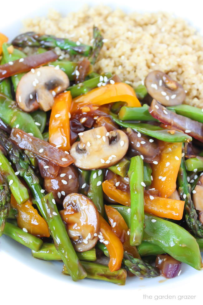 Quinoa stir fry with vegetables in a white bowl