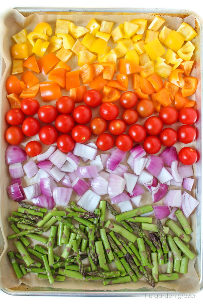Sheet pan of chopped rainbow vegetables ready to roast