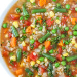 Bowl of vegan vegetable barley soup topped with parsley