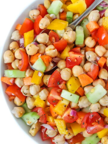 Vegan chickpea salad with vegetables in a bowl with spoon