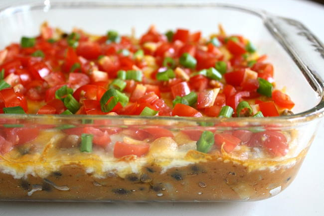 Vegan bean dip in a glass dish topped with tomatoes and green onions