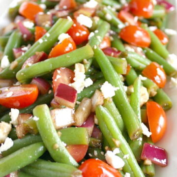 Balsamic green bean salad with onion and tomato on a white plate