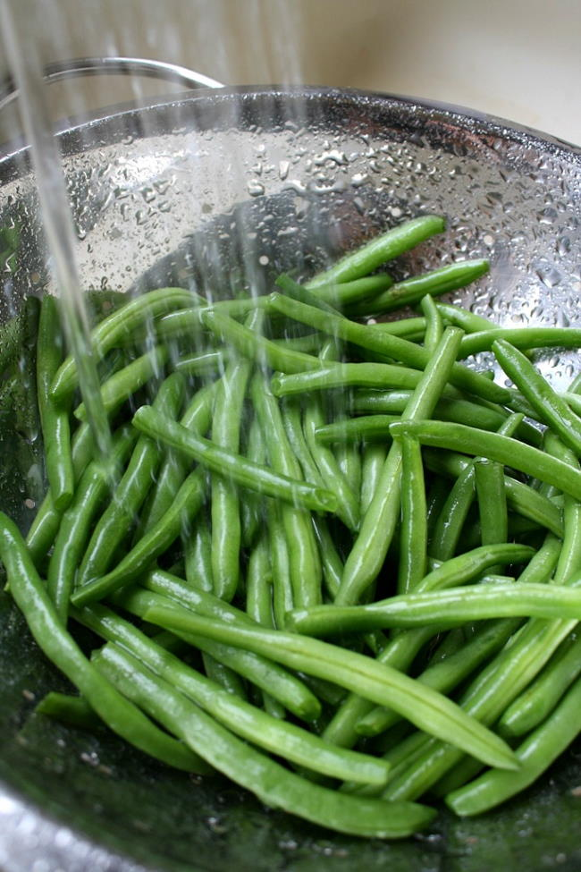 Fresh green beans being rinsed in a colander