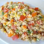 Quinoa Vegetable Salad tossed with lemon-basil dressing on a plate