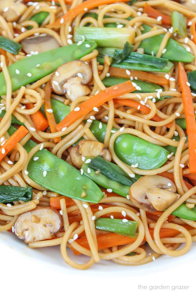 Bowl of vegan pasta with snow peas, mushroom, and carrot