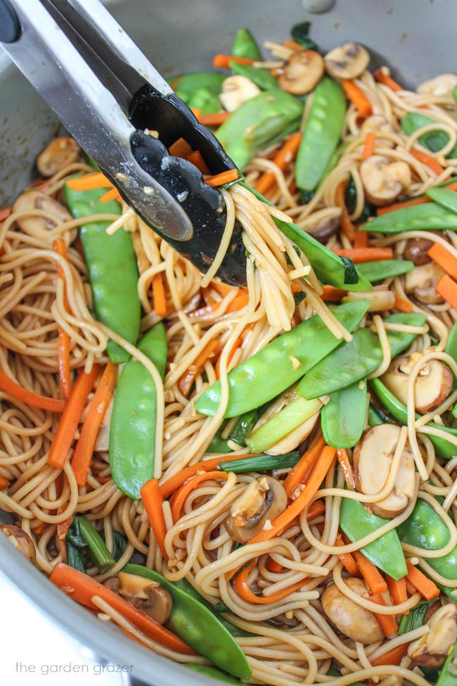 Asian garlic spaghetti with snow peas, mushrooms, carrots in a pan
