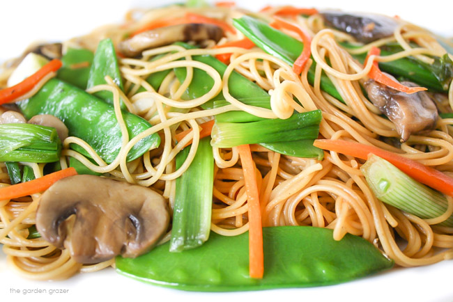 Asian spaghetti on a plate with carrots, mushrooms, snow peas
