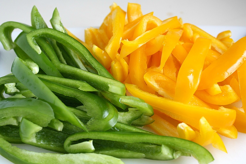 Sliced yellow and green bell peppers on a cutting board