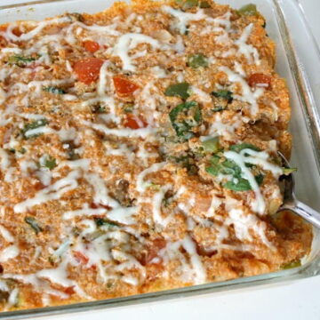 Vegan pizza quinoa casserole in a large glass baking dish with spoon