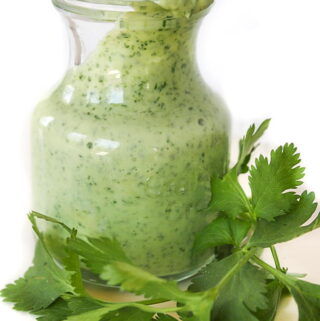Jar of creamy cilantro-lime dressing with fresh cilantro in front