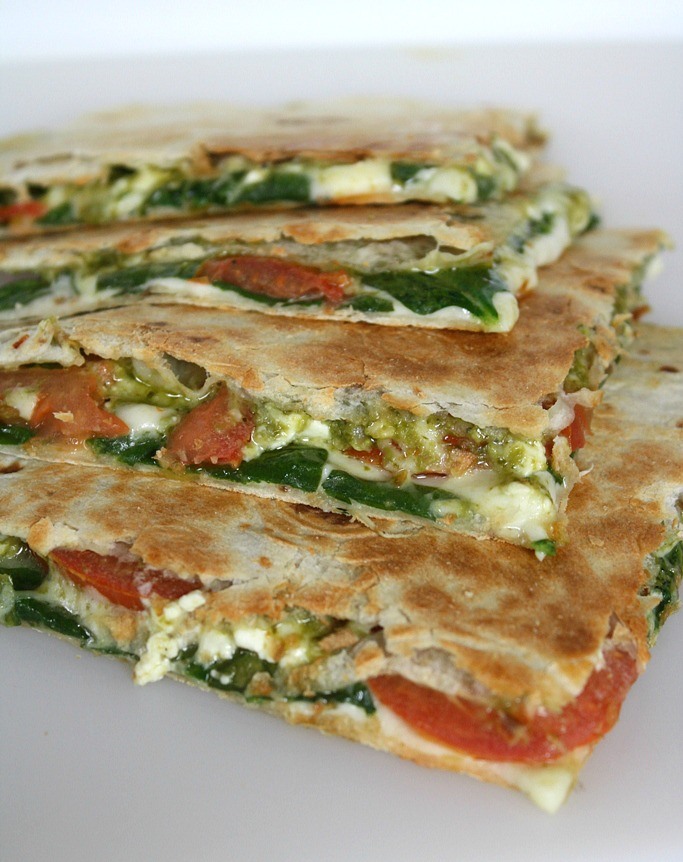 Vegan pesto quesadillas with tomato and spinach cut in half