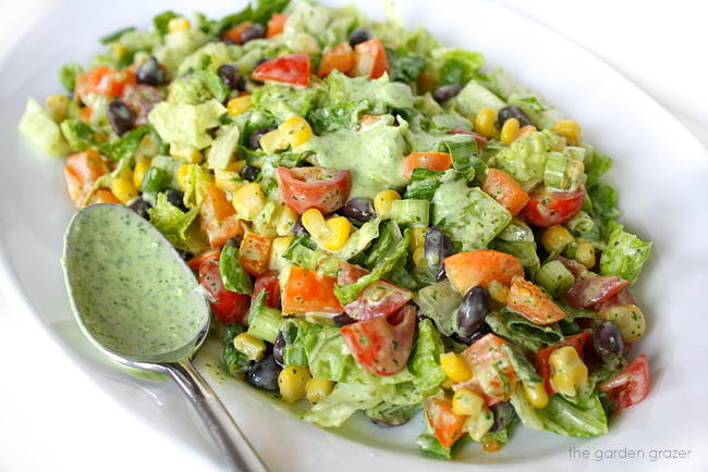 Chopped Salad tossed with creamy dressing on a plate with spoon